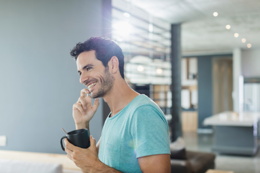 Happy man talking on cell phone and drinking coffee at home